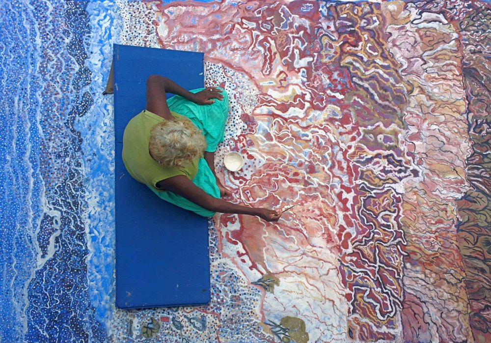 Mavis Ngallametta painting large-scale work. Photo: Gina Allain.