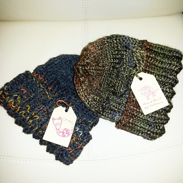 The green and blue alpaca hand knit hats ready, labeled for shipping to their knew owners.