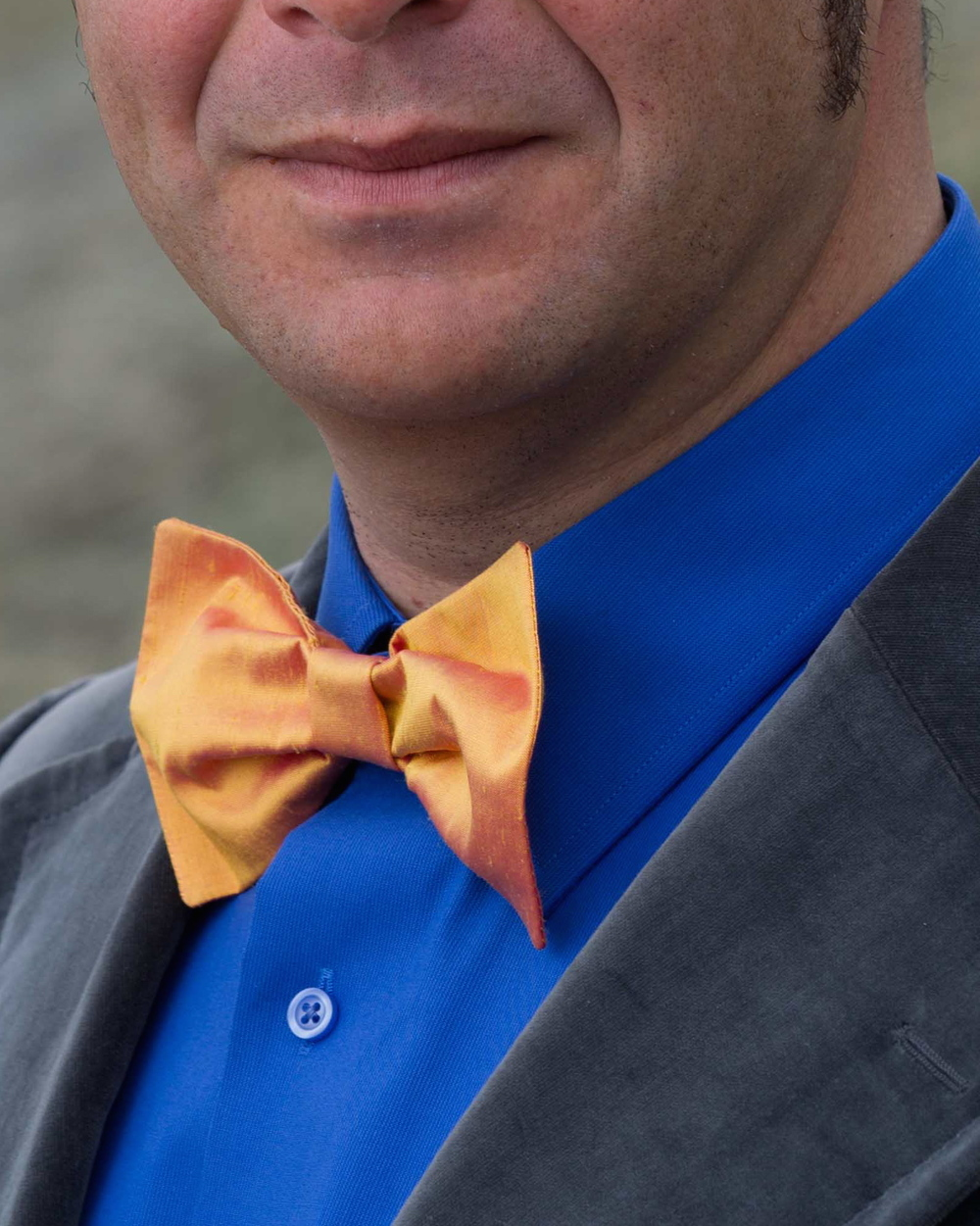 Close up of the gold bow tie in chameleon raw silk yellow and orange