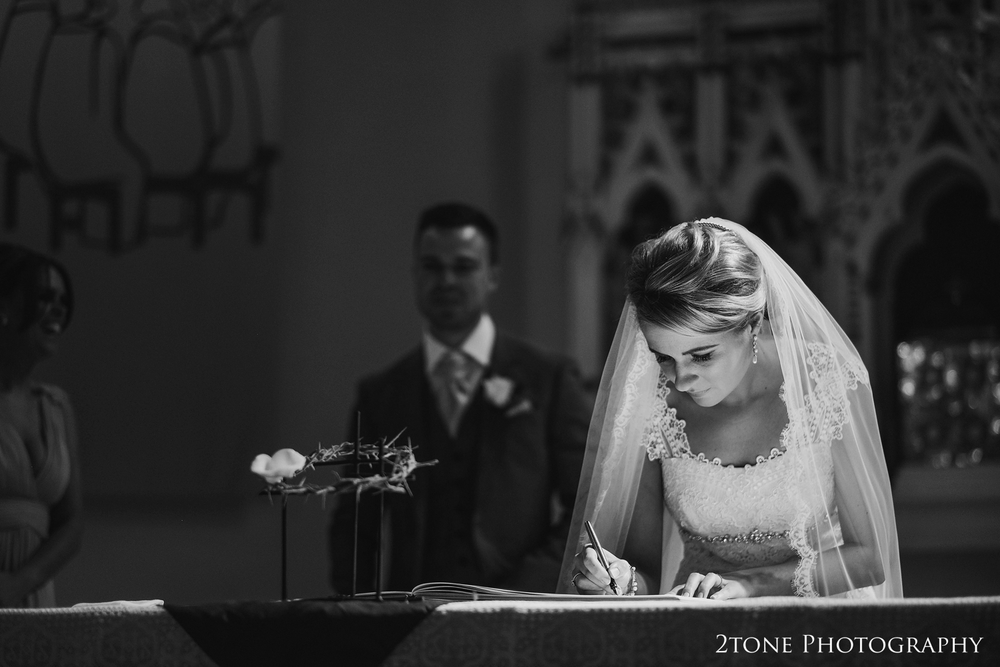 The directional light from the stained glass windows has come out to play again as Danielle signs the register.  I love the dramatic effect of this kind of lighting on a scene like this.