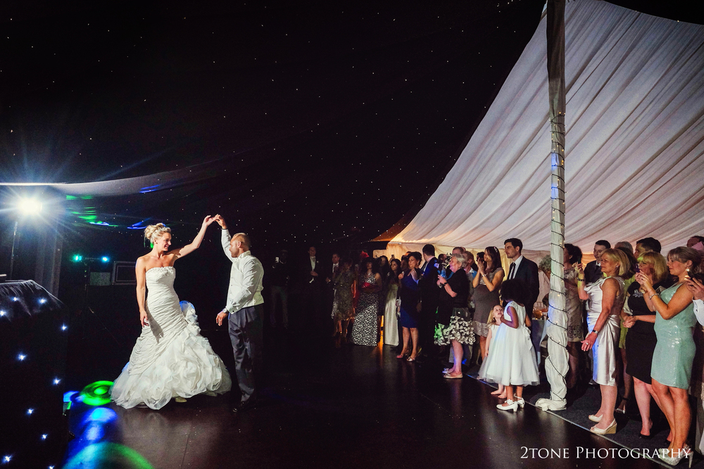 I love this shot, great light and great atmosphere.  I love how the bride and groom have their own space with what could be a sky full of stars above them with their family and friends standing by watching and enjoying their first dance.