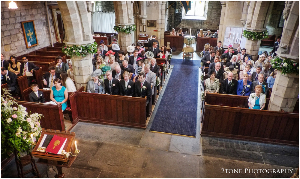 The classic interior of the Holy Trinity Church in Embleton filled with wedding guests and a perhaps slightly nervous groom await Kristen's arrival.