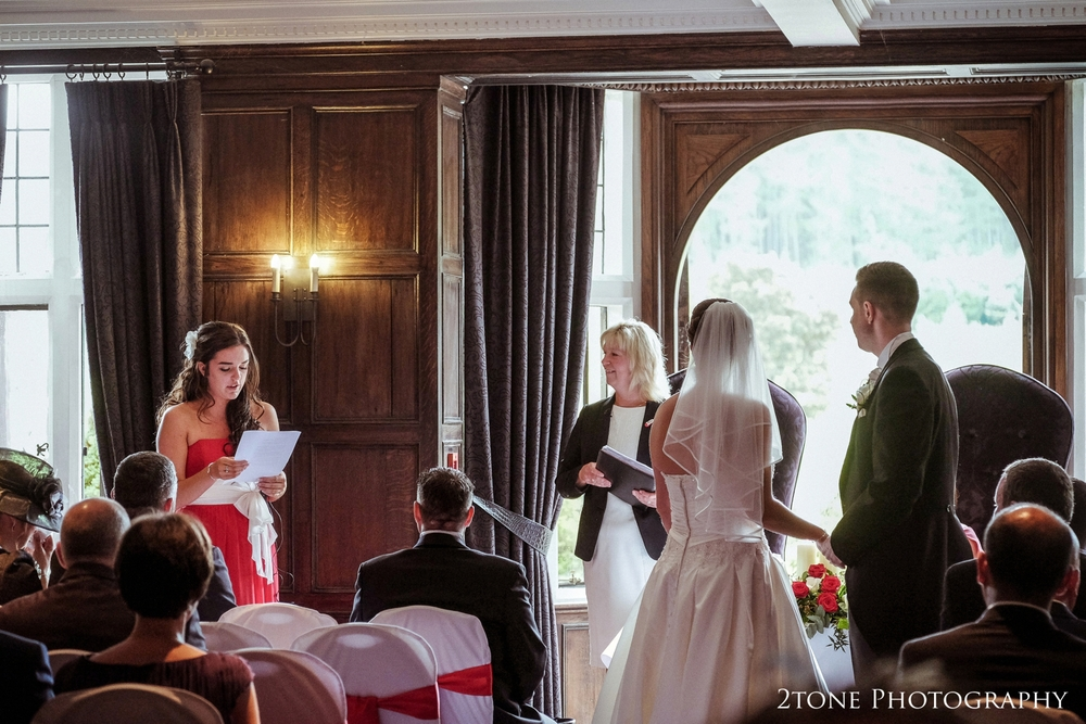 Hannah's sister Robyn stands to give a reading during their wedding ceremony as they look out over the northumberland countryside.