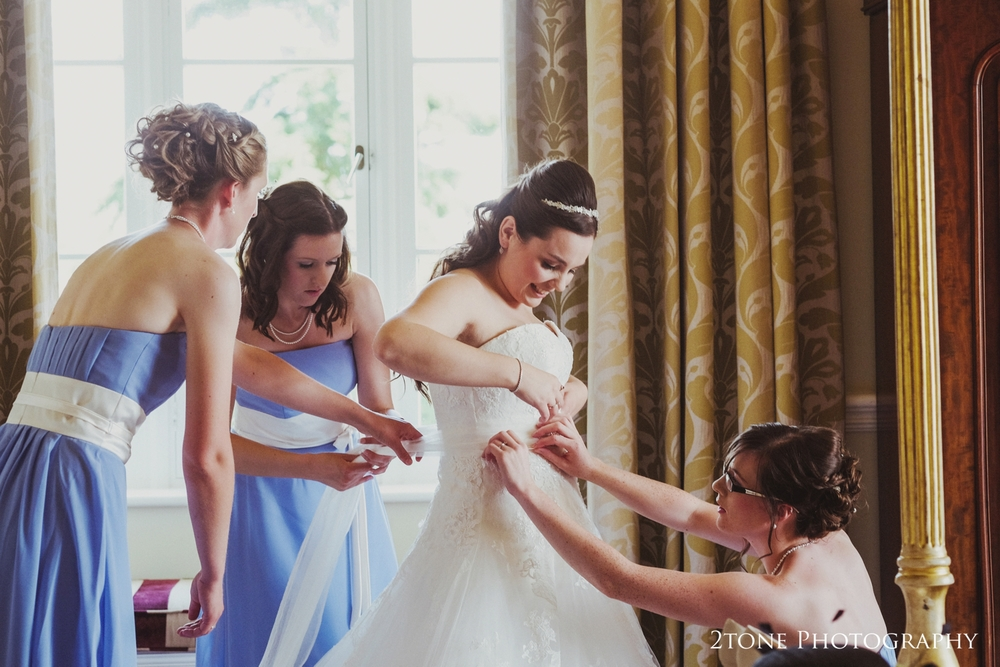 Natalies lovely bridesmaids helped her into her stunning wedding gown in Matfen Hall's bridal suite.