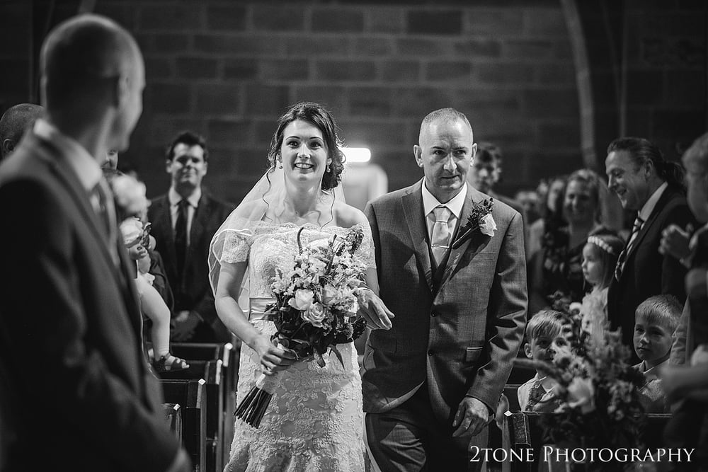 The Bride walks down the aisle in St Oswin's Church in Newton Under Roseberry by 2tone photography www.2tonephotograpy.co.uk