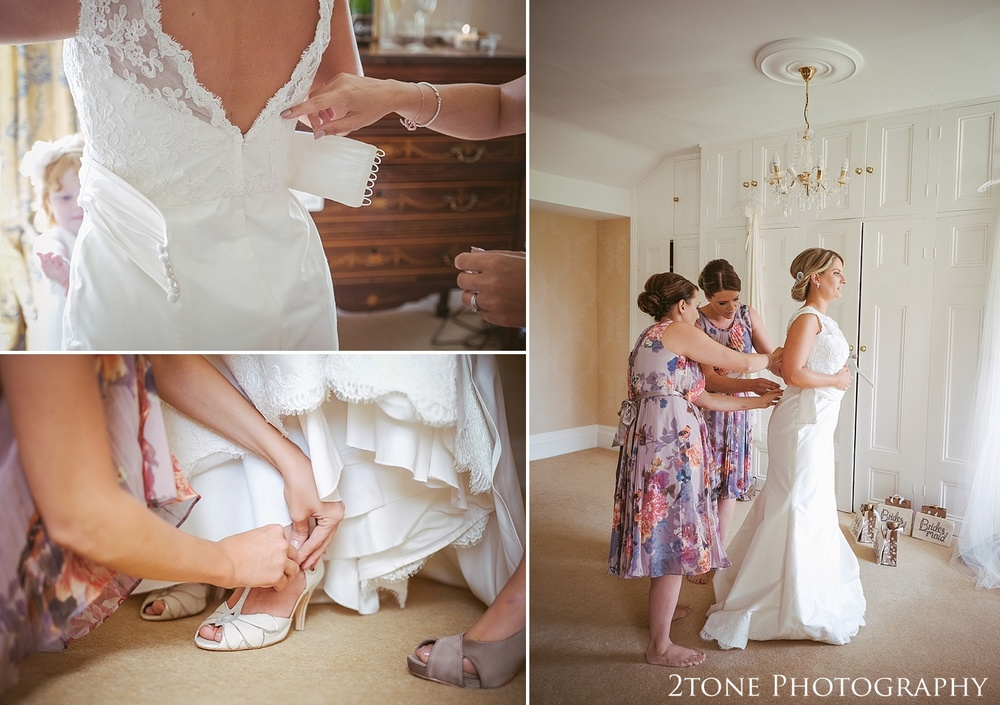 Bride getting dressed.  Wedding photography at Guyzance Hall by wedding photographers www.2tonephotography.co.uk