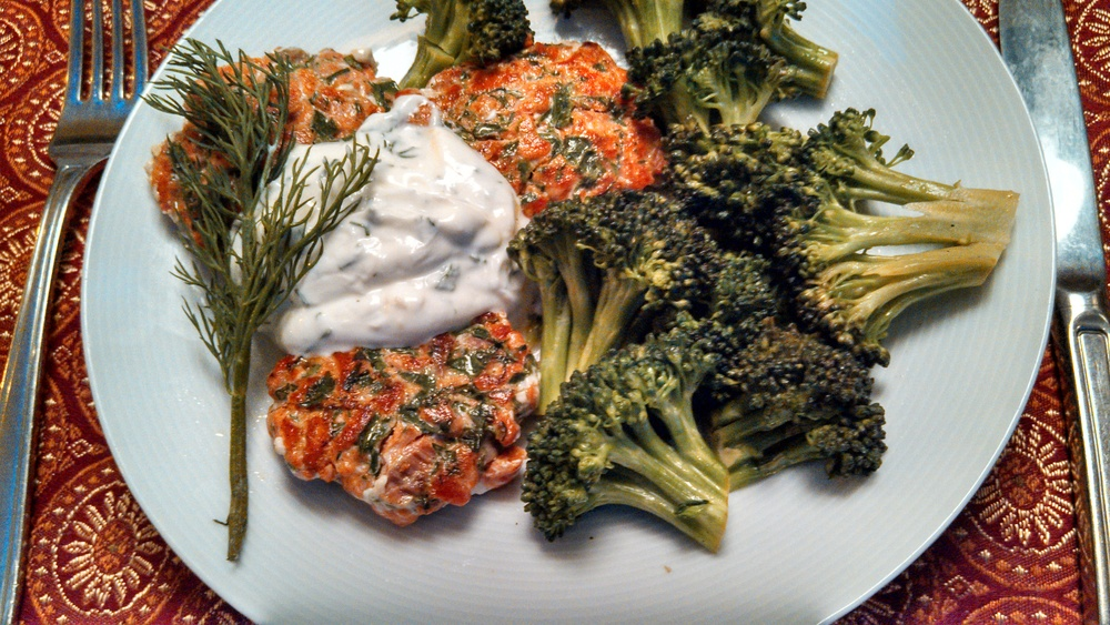 Home made salmon burgers with yogurt sauce and broccoli