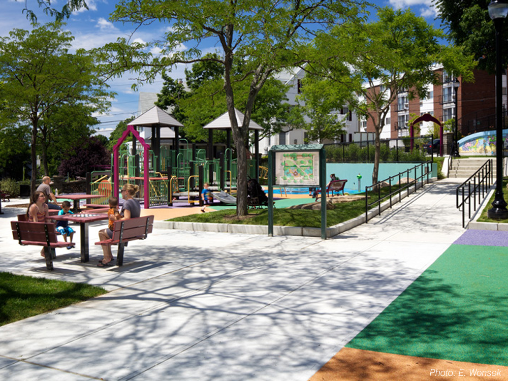 Formerly separated onto two levels, this park has been re-connected through our plan. An accessible route now links the refurbished play area and seating on the lower half, with a revitalized upper level that replaced an unusable basket-ball court with open lawn, a bocce court, picnic tables, and a winding pathway. Inspired by a recent mural on the uppermost wall, CBA's design uses the same vibrant colors, echoes similar shapes, and draws out details such as a blue bear's face to form the basis of the spray area.