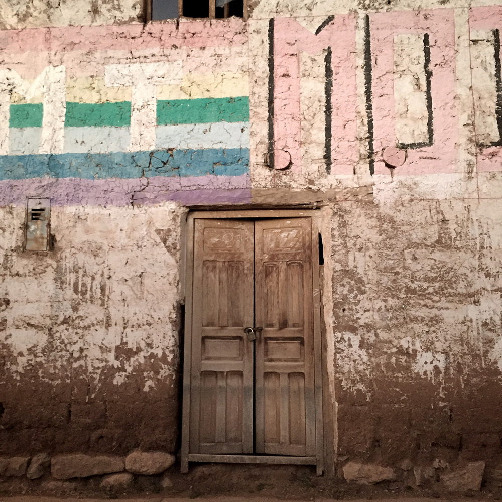Typical wood door of the suburban pueblos. This construction is of local sun-dried mud brick with plaster.