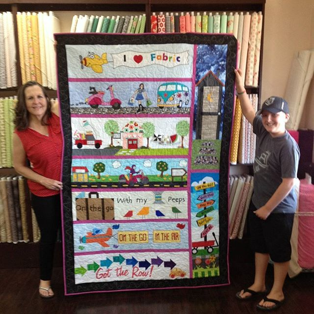 "Congratulations to Mary Kate Erickson who won our Row by Row Challenge---both prizes. She was first to bring in a finished quilt and first to use our row in a finished quilt. She won a stack of 25 fat quarters and the book ""12-Pack Quilts"" by Barbara Groves and Mary Jacobson of Me and My Sister Designs. Her grandson Maxwell is working on the row by row junior."