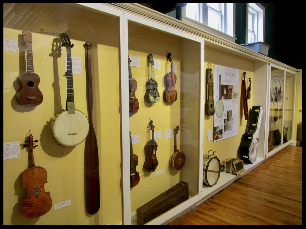A multitude of musical instruments fill the walls of the TAUNY Gallery, Canton, NY.