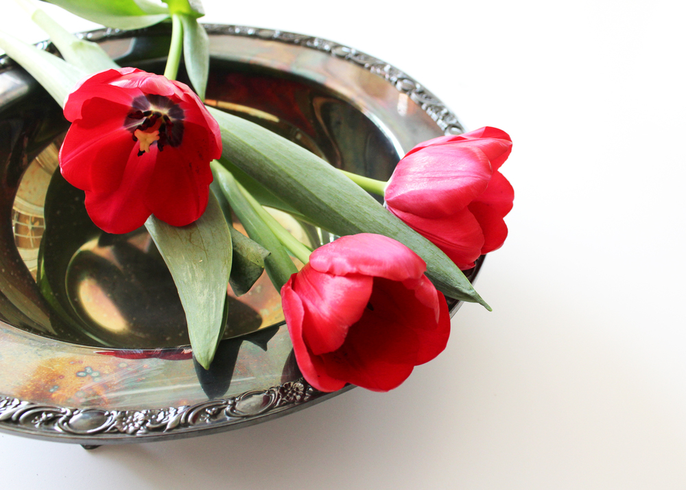 Lay flowers gently in a thrifted silver serving bowl