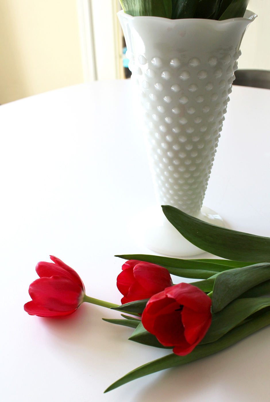 Introduce a milk glass vase to fresh greenery