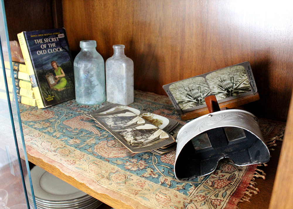 antique medicine bottles and a stereoscope viewer with pictures from the early 1900s