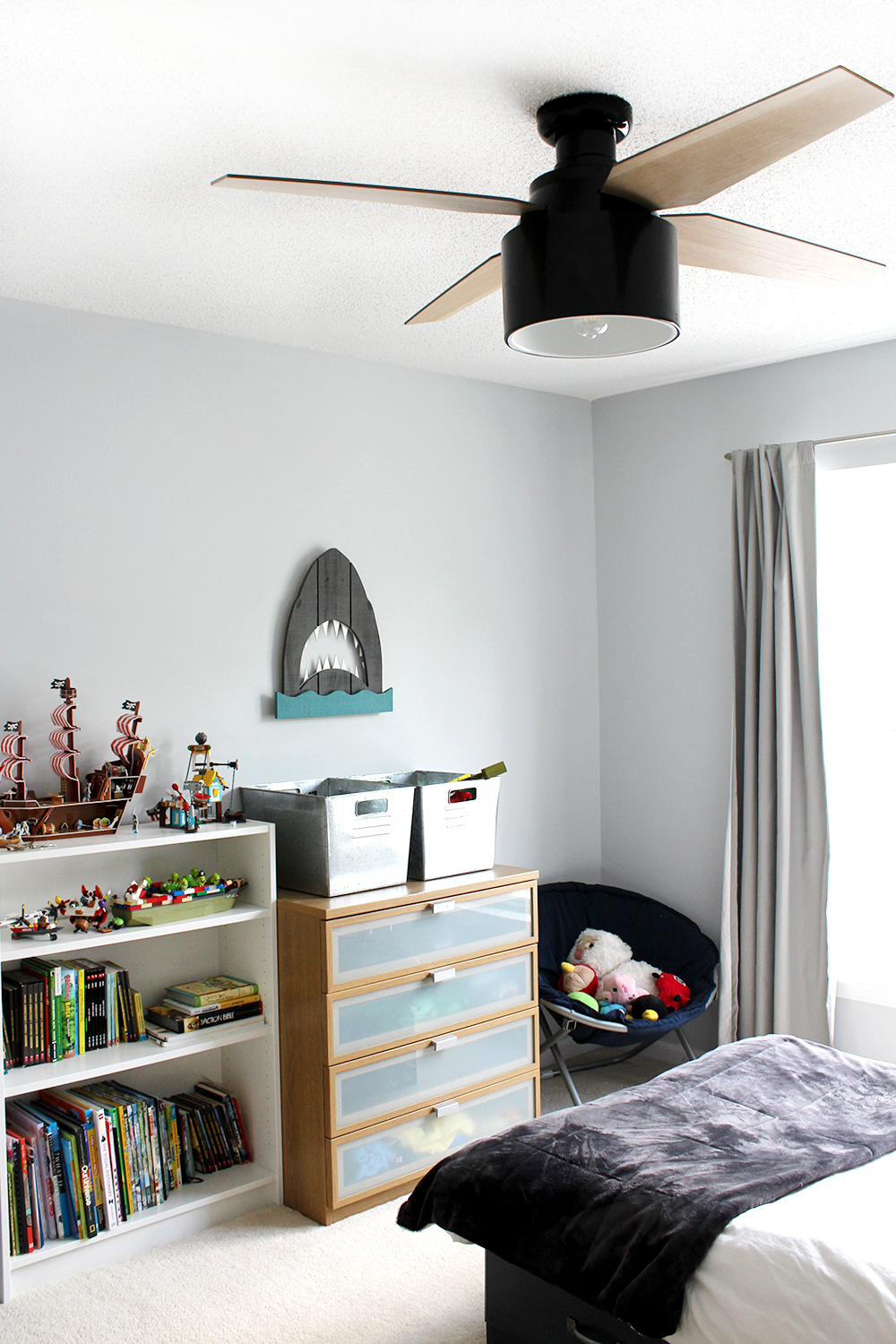 preteen boy's room with blue-grey walls and modern black ceiling fan