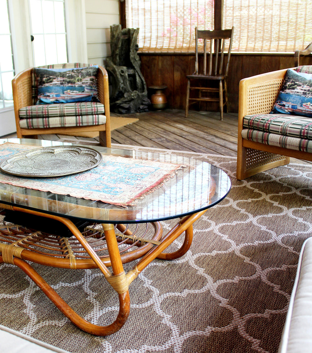 barrel chairs (thrift store find) with vintage coffee table on a screened porch