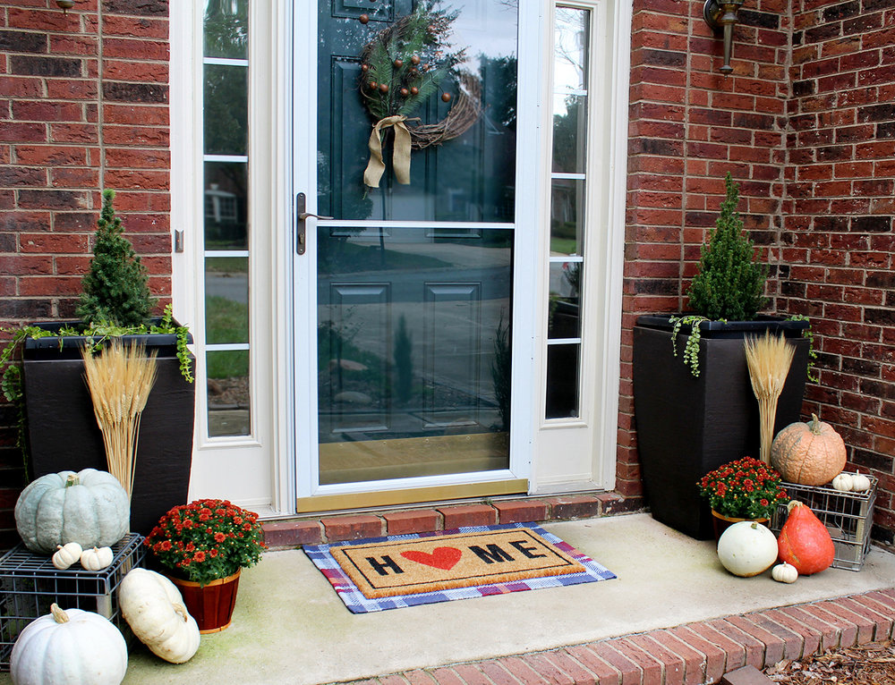 Decorate a Fall front porch with mums, pumpkins, and wheat--check out these practical tips! #autumndecor #falldecor #pumpkins