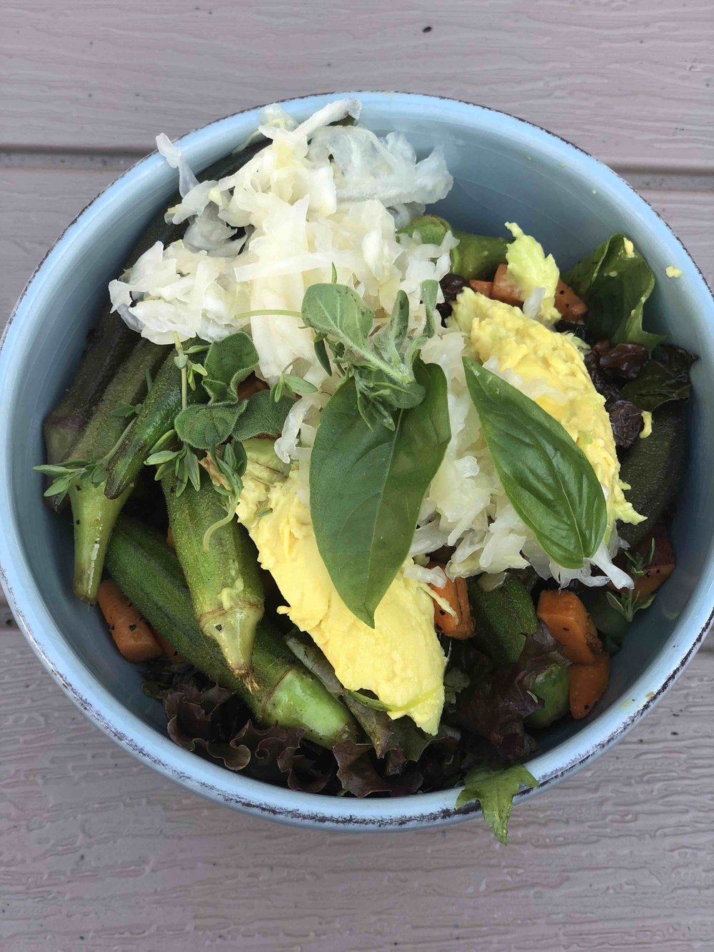 Okra Bowl with sauerkraut, avocado, sweet potato and farmers market lettuce topped with garden herbs