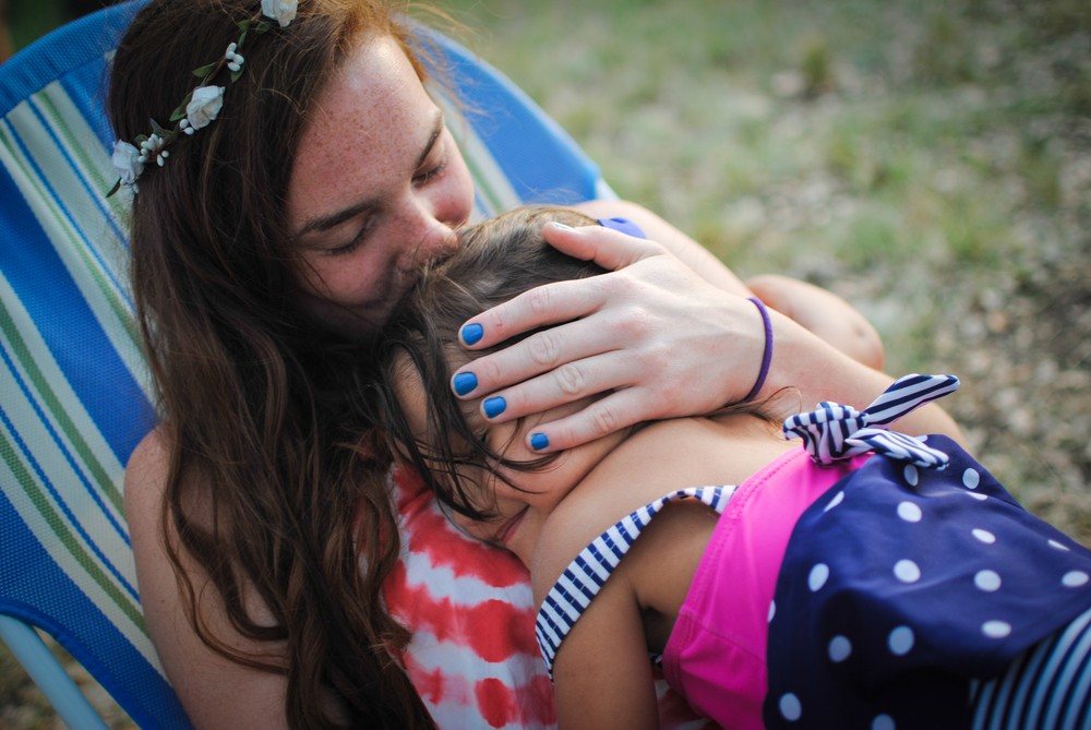 Claire and Maiya snuggle while relaxing at the campsite.