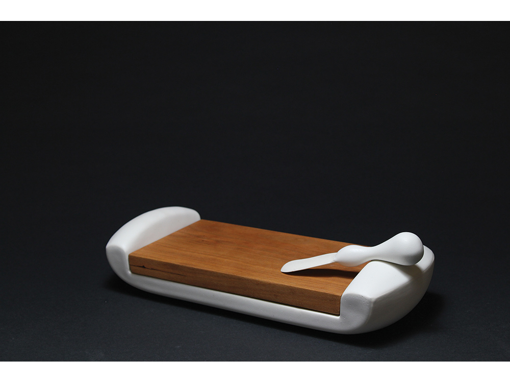 Nick Moen and Mimi McPartlan A dreamy, cloud-like porcelain form cradles a cherry cutting board, complete with porcelain knife. Moen and McPartlan developed the table-ready cutting and serving piece in Moen's studio in Ashe­ville, North Carolina.