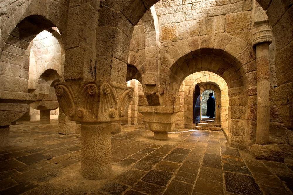 Cripta sustentada por gruesos pilares cruciformes con capiteles de decoración vegetal fuertemente geometrizada.