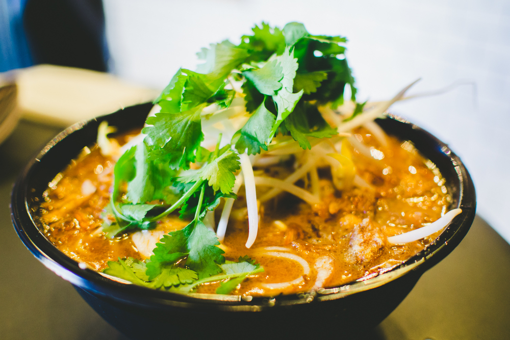 'HH' laksa: rich spicy soup with rice vermicelli noodles, coconut poached chicken, prawns, and sweet tamago egg topped with coriander - $9.90
