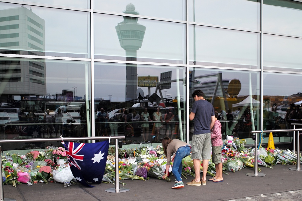 Mourners of the 298 people aboard Flight MH17 leave flowers in a makeshift memorial at Amsterdam's Schiphol Airport. Photo: Roman Boed via Flickr Creative Commons