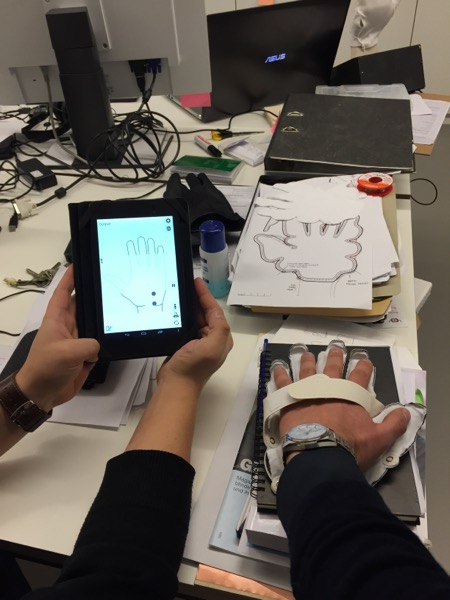 Rechts der 4. Prototyp des Handschuhs,auf der App kann man mitlesen, welche Sensoren beim Empfang vibrieren.