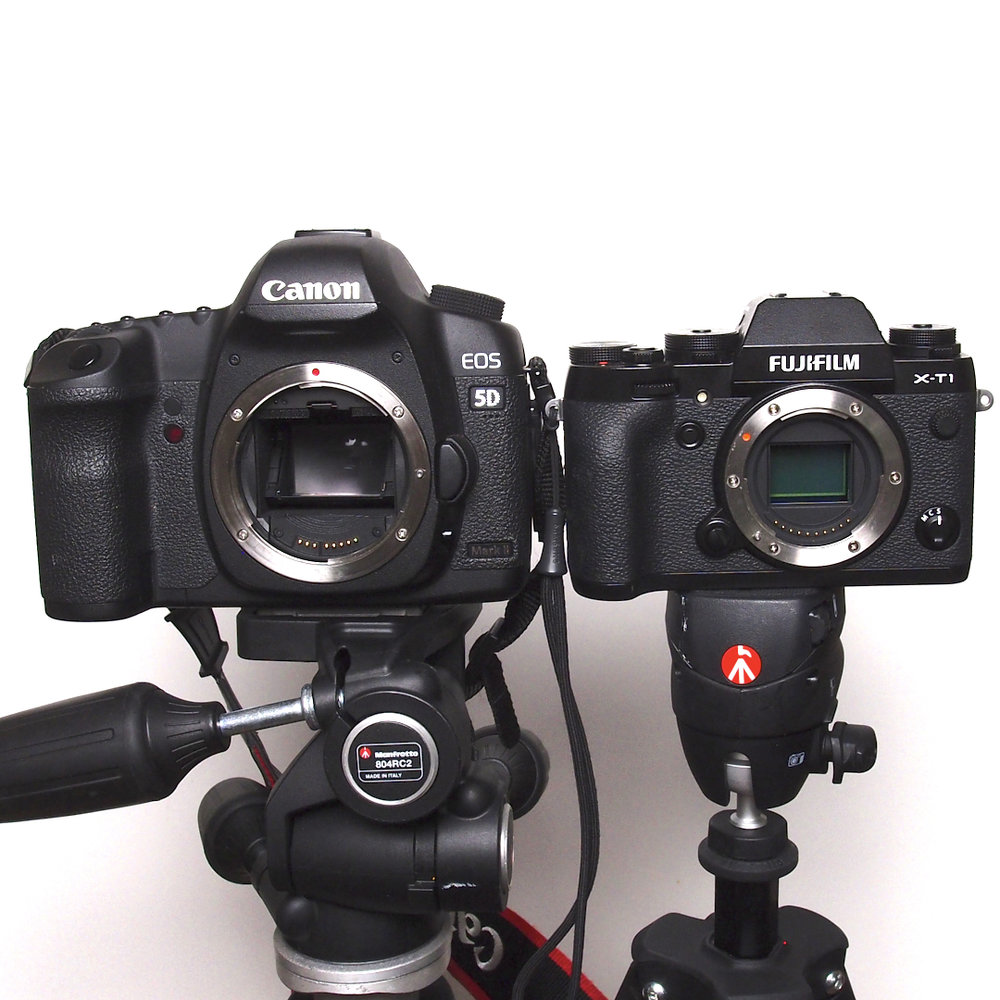 Links:  de Canon 5D mark II spiegelreflex (dslr) - je kan de gekantelde spiegel zien zitten,daar achter zit de sensor. Mede door de spiegel is deze camera groter dan de Fujifilm.  Rechts:  de Fujifilm X-T1 mirrorless camera - je ziet de sensor vlak achter waar de lens normaal zit. Mede omdat dit ontwerp niet diep hoeft te zijn is de camera een stuk kleiner dan de Canon. Dek normaal gesproken de lensopening altijd af met een lens of bodydop, om vuil en beschadigingen op de sensor te voorkomen!