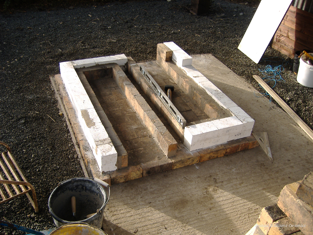 Woodkiln base with fireboxes and flue channel