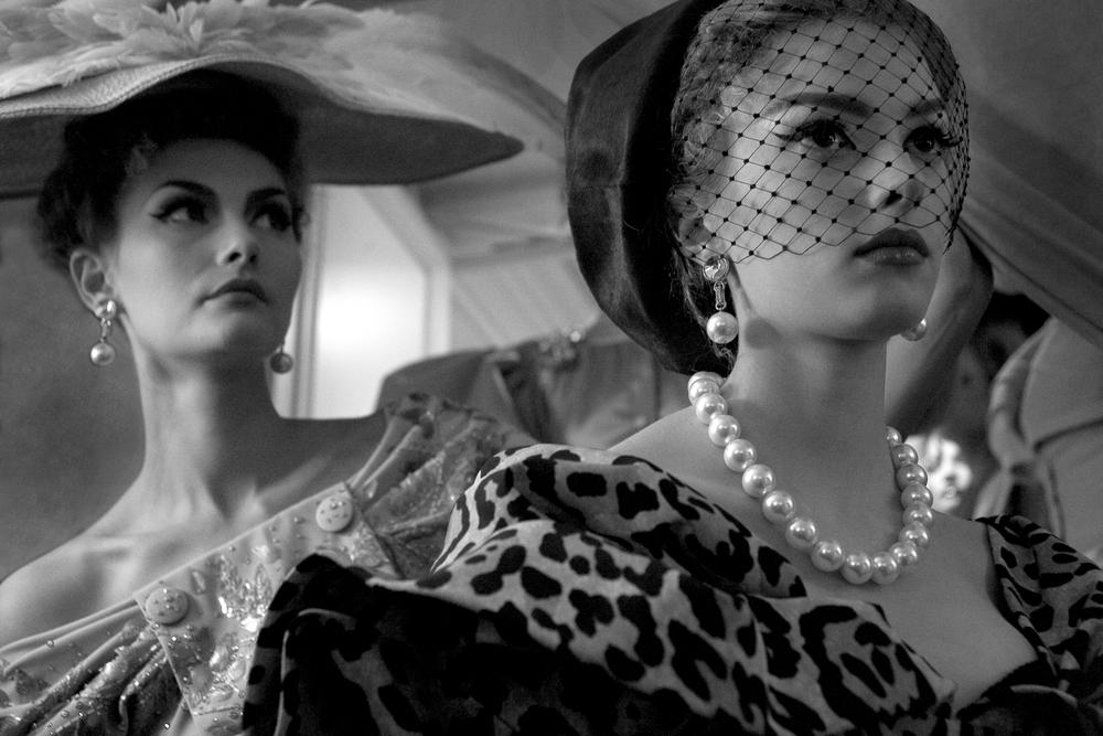 Las imágenes del backstage de la colección de costura de Christian Dior muestran a dos modelos con los recargados vestidos de la colección de 2009, que retomaba a manos de John Galliano, la sofisticación de materiales bordados y con pedrería del maestro Dior, mientras que conjugaba su New Look con faldas abullonadas y cinturas ajustadas. Las perlas y los sombreros planos con gran ala son característicos de los años 50.