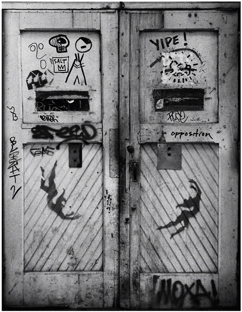 "Fernando Natalici's ""The Door"" (New York, circa 1979) represents one of only two known photographs in the world featuring the early graffiti work of a young Jean Michel Basquiat & Keith Haring together on one image. The work was recently recovered as part of an archive of previously lost photo works, unseen for over 25 years, documenting the emergence of the Lower East Side art scene. The work combines the two most iconographic images of Haring & Basquiat's career, while also uniquely presenting the work of two other greats, Whitney Biennial featured artist David Wojnarowicz & five time Brazilian Biennial artist Alex Vallauri."