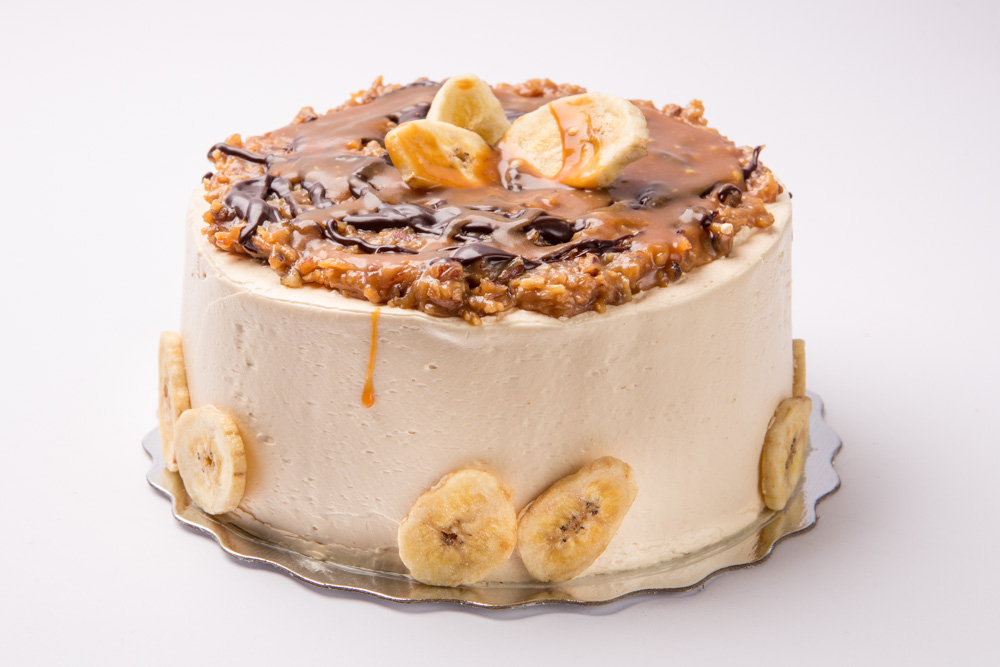Banana Colada   Moist banana cake layered and topped with coconut, pecans and caramel.