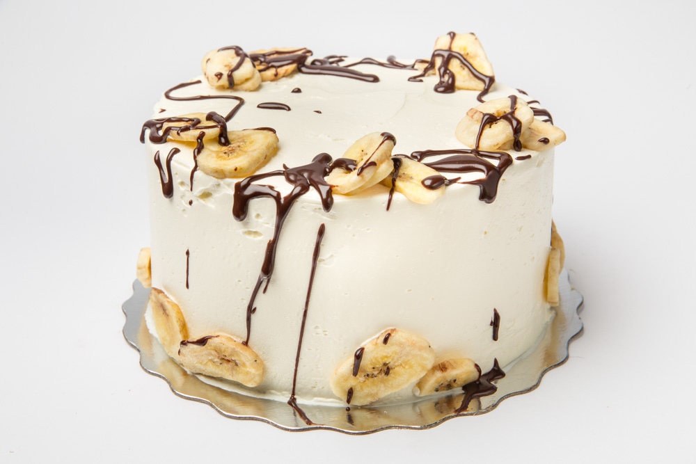 Bananarama   Sweet, moist layers of banana cake iced in a cream cheese frosting. Topped with crunchy banana chips and splashes of chocolate ganache.