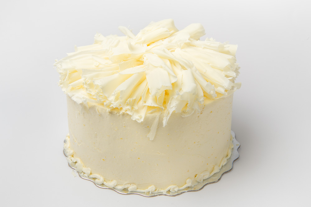 Lemon Cream Layers of lemon curd, white chocolate mousse, and delicate chiffon cake iced in lemon buttercream and topped with fluffy white chocolate curls.