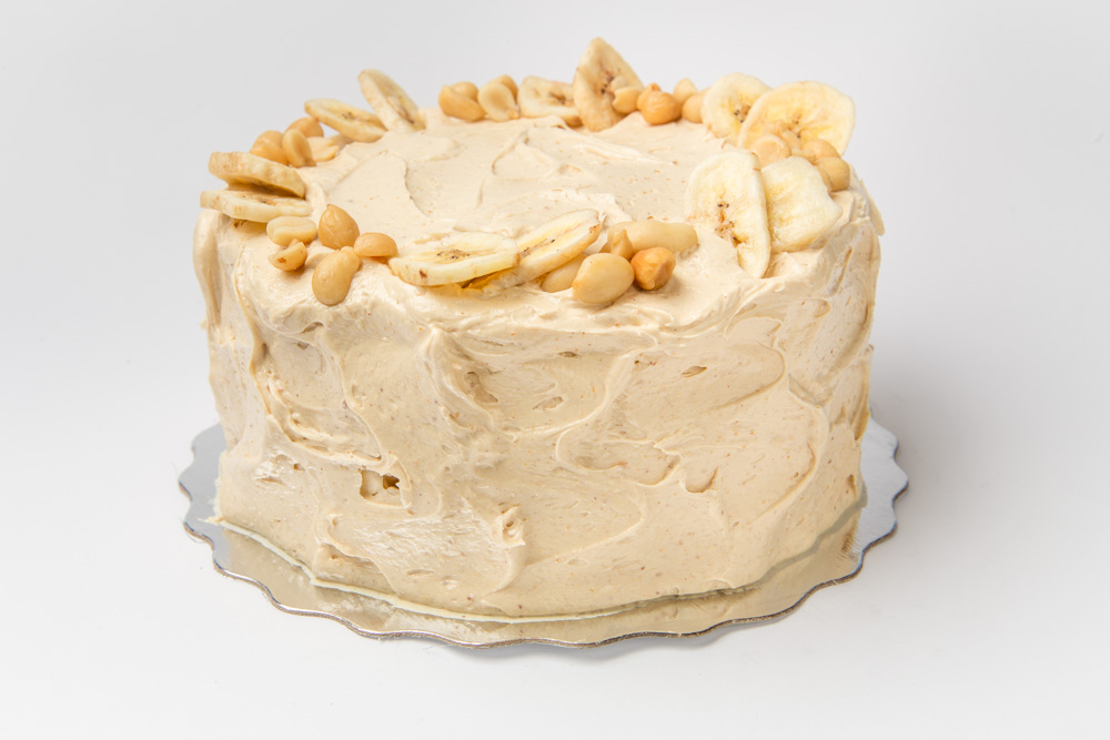 Monkey Business   Banana cake iced in a creamy peanut butter frosting. Topped with toasted peanuts and banana slices.