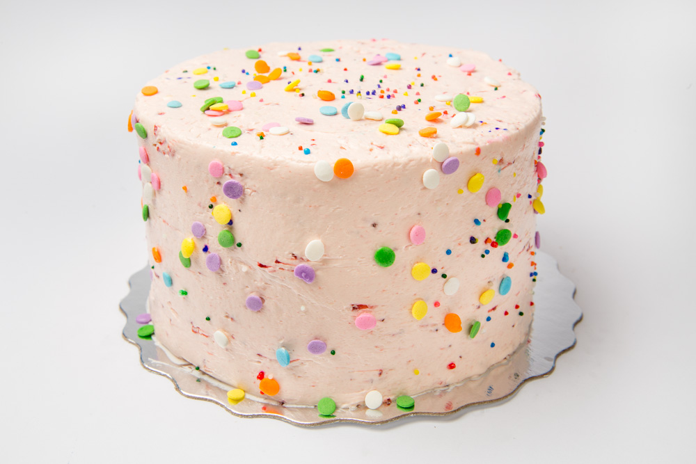 Strawberry Vanilla   Our moist vanilla cake iced in our strawberry buttercream. Topped with colourful confetti.
