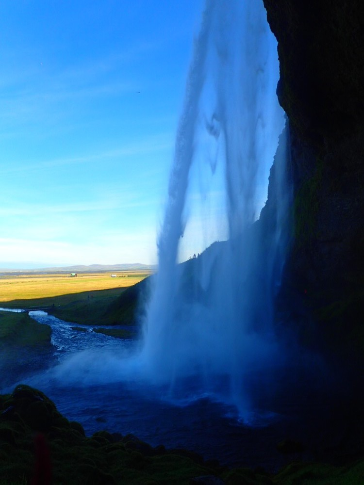 A waterfall from behind, as part of the Ring Road in Iceland