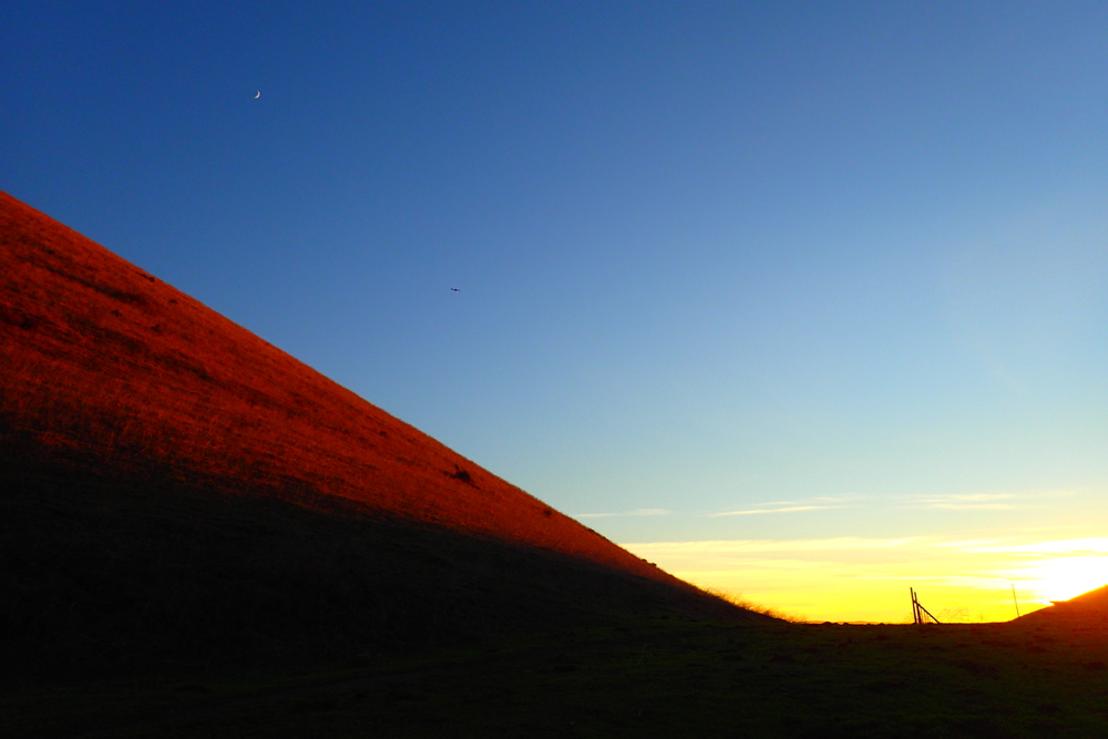 The sun sets over the mission peak trail as a plane passes below the moon