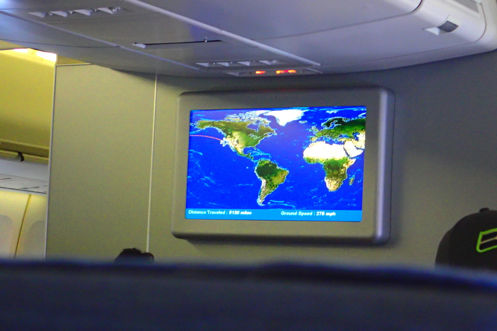 Peering over the airline seats at the world map