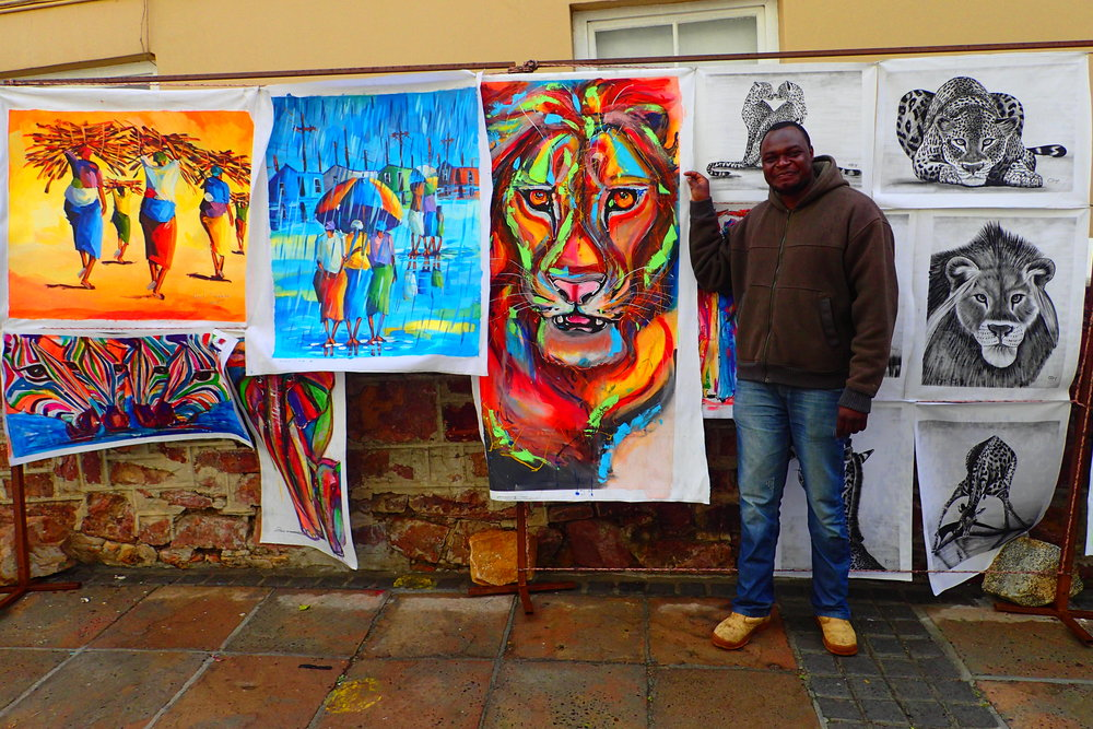 Asanoo posing with his and his brother's artwork