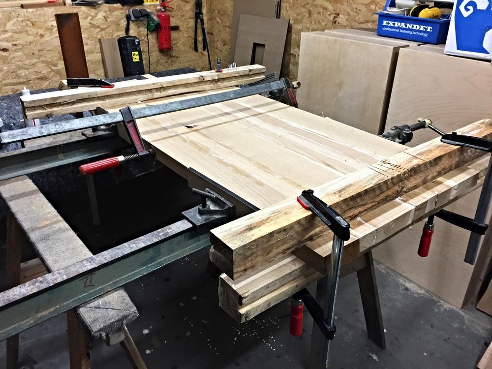 """Når kiks/dominobrikker og lim er sat i og påført, skal plankerne """"tvinges"""" sammen. Til dette er det optimalt, at bruge en kombination af dørtvinger og skruetvinger."""