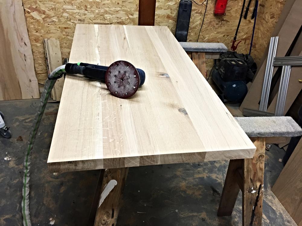 Når limen er tørret og overskydende lim er fjernet, saves bordet i ønskede længde, og slibningen påbegyndes.