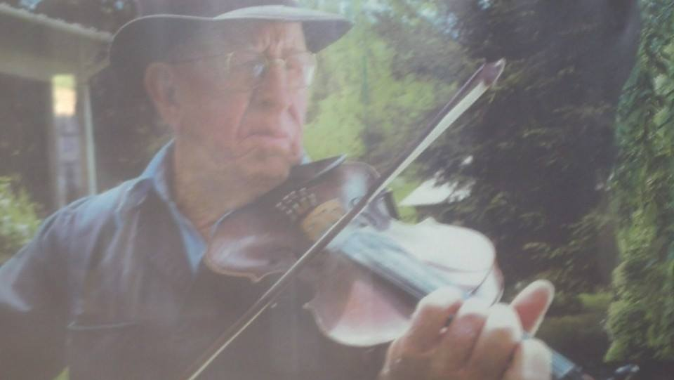 "Bitt Rouse (1923–2007) by Jesse Graves   Bitt Rouse was the only one-handed fiddler I ever met. He played old-time ballads and mountain tunes, learned when he was a boy, and when he had both of his hands. The way Bitt lost his right hand must have been unimaginably painful. For six hours, he knelt beside a corn picker that had caught his shirt sleeve and pulled him into the machine, until a neighbor finally heard him calling for help. My father remembers working for his cousin Bitt when he was a boy in that same field, plowing with a horse for 50 cents a day. My dad thought that was good money in the late 1940s, especially for a boy who should have been in school.   His real name wasn't Bitt at all, but Palmer Steiner Rouse, a collection of three of the oldest family names in Union County, Tennessee. Doc Palmer delivered most of the babies in Sharps Chapel for a generation at least, and became the namesake for many of those children (like my father's oldest brother, Eugene Palmer Graves). The Steiners may have been the only family in the community to have acquired more land than the Rouses. How he came to be called ""Bitt"" is anybody's guess, though almost all the country men I knew from his generation had a nickname—some of my own great-uncles were known as ""Cotton"" and ""Mutt.""   Bitt Rouse died at 84 years of age, on his way to unlock the doors of the restored one-room Rush Strong schoolhouse, where a group of local musicians played for a monthly barn dance. In cold weather, Bitt went to the school early, to get the wood-stove burning before the crowd arrived. He kept a kind of fire going in the old-time music he played, as well, like the hearth-fires brought across the ocean to the New World. Bitt tended the flame until his very end, and that seems like a good way to go out after 84 years."