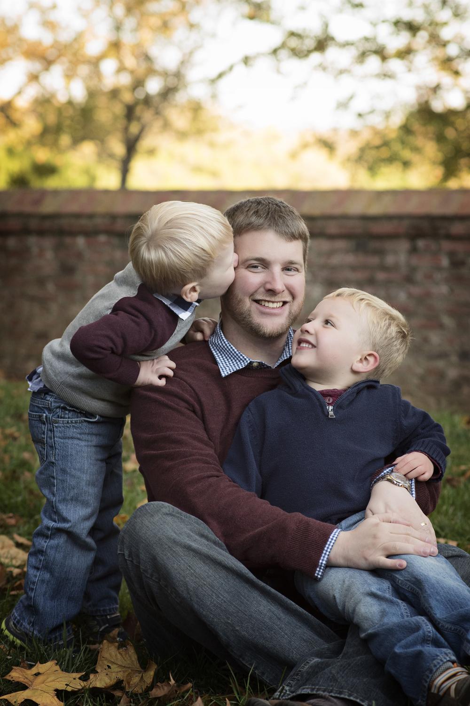 father with two sons hug and kiss Nova portrait photographer Kate Montaner Photography