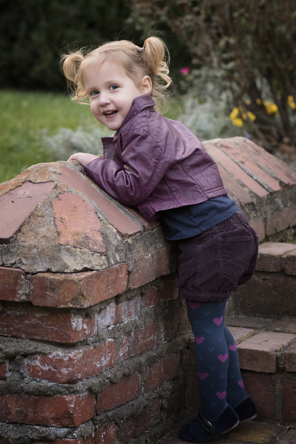 adorable little girl with pigtails and pink tights Childrens Photographer Kate Montaner
