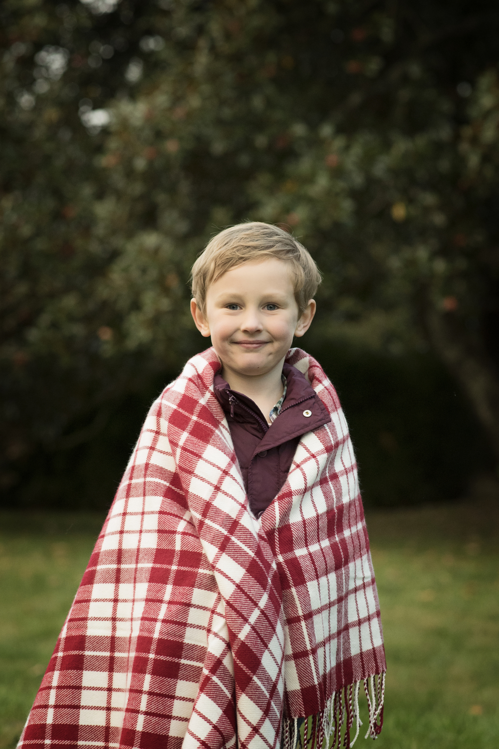 Little boy in christmas blanket Kate Montaner Photography LLC