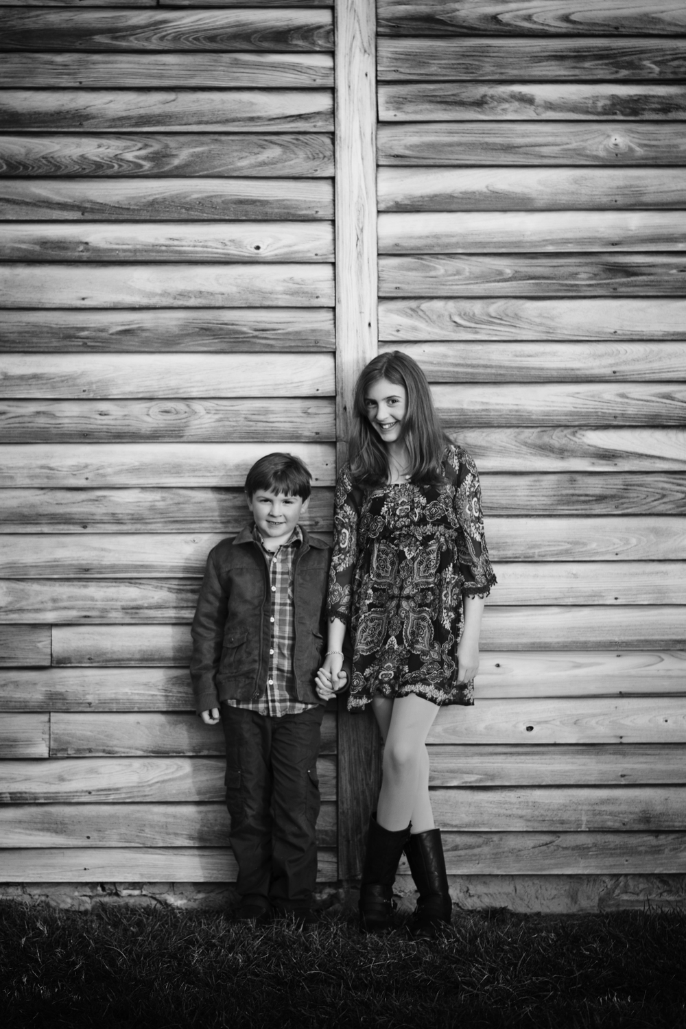 Siblings in front of barn childrens black and white photography Kate Montaner