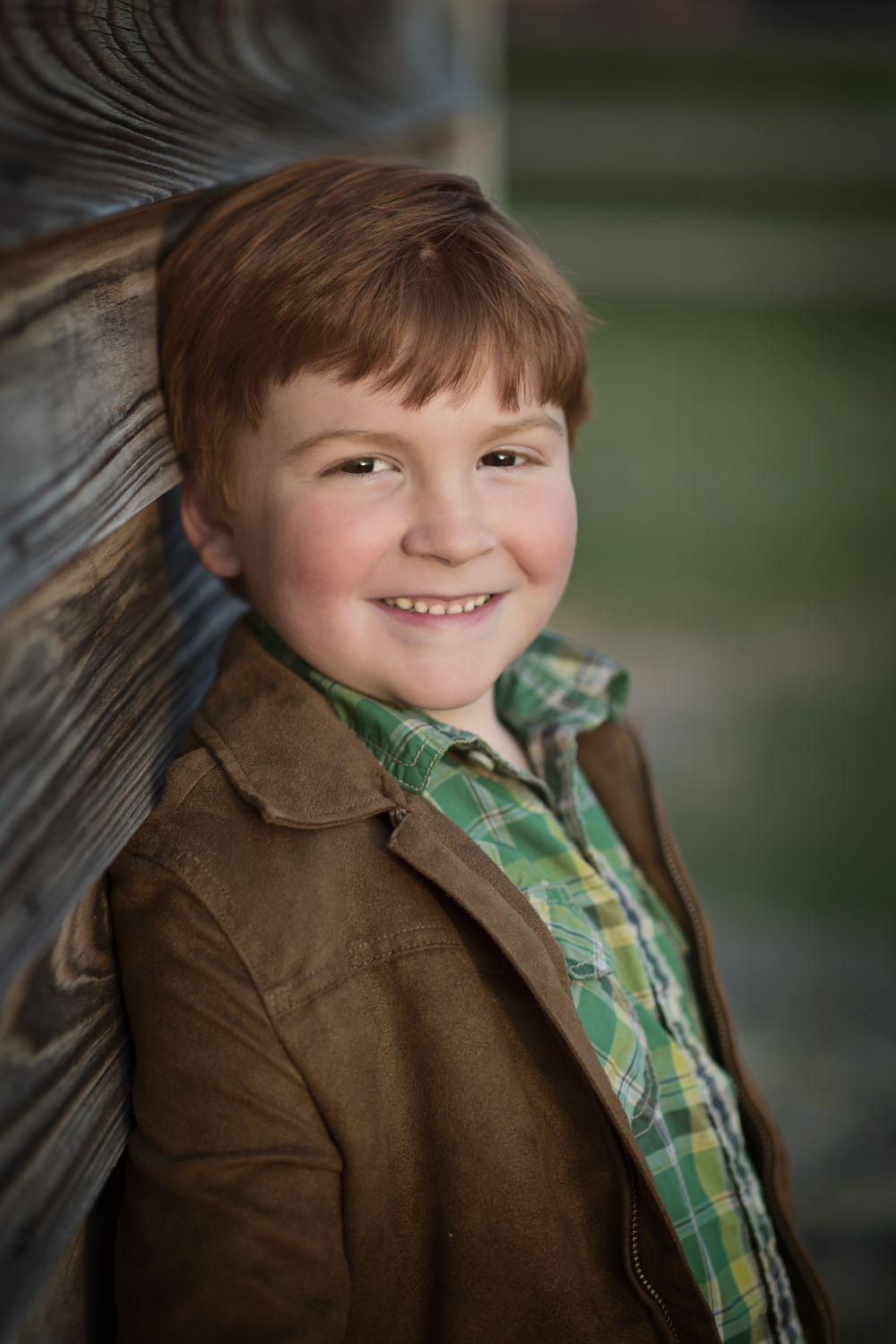 Smiling Redhead boy with freckles with barn Kate Montaner Photography