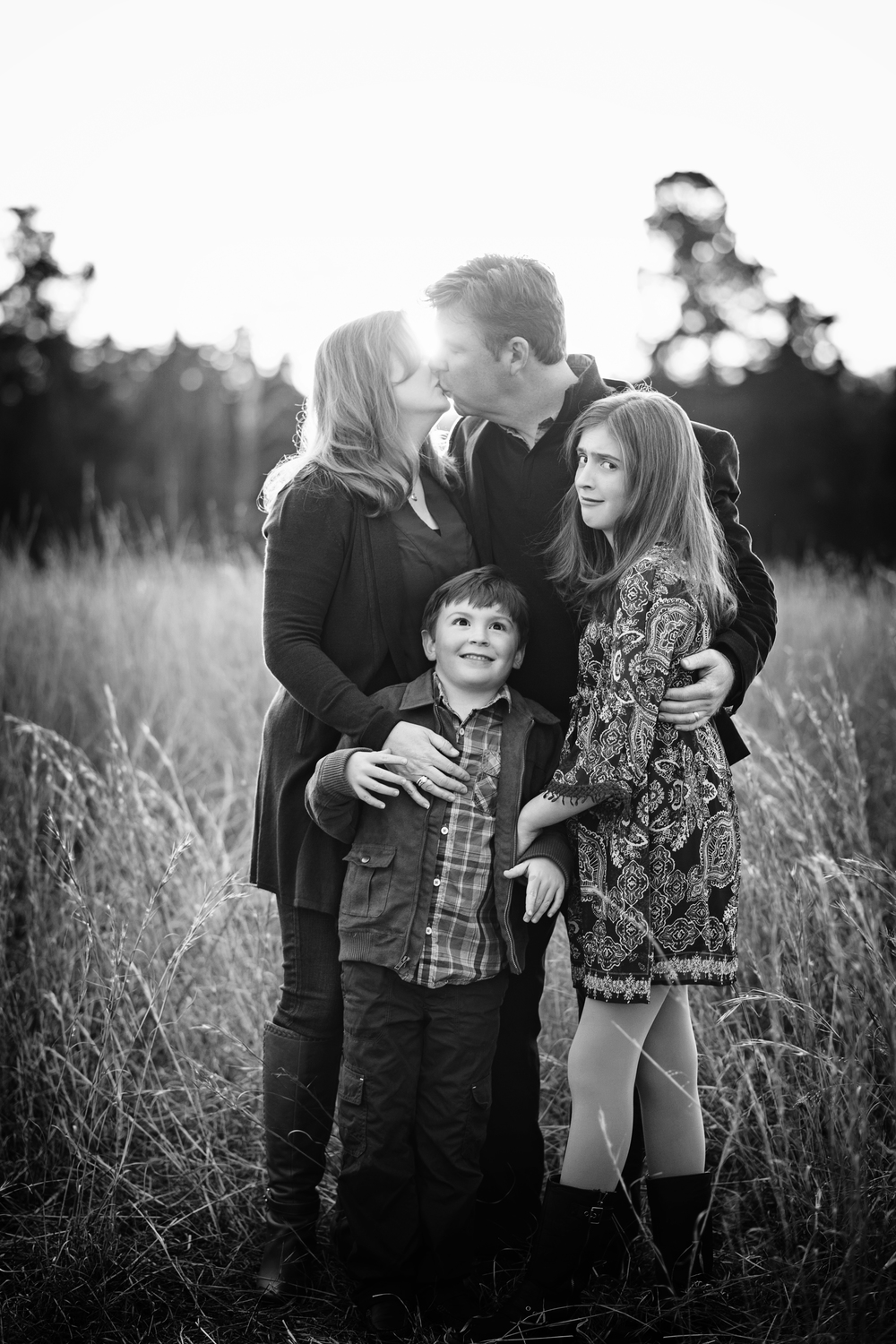 couples kiss at sunset with children making funny faces Kate Montaner Lifestyle Photographer